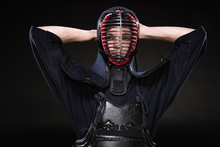 Kendo fighter in armor touching helmet and looking at camera on black Stok Fotoğraf