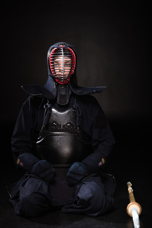 Kendo fighter in helmet with bamboo sword sitting on black