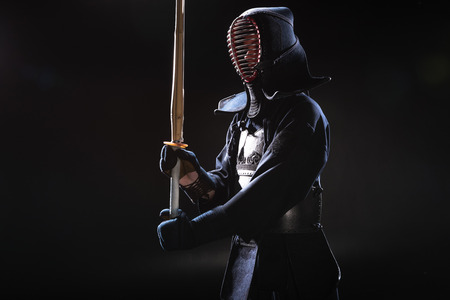 Kendo fighter in helmet holding bamboo sword on black Stock Photo