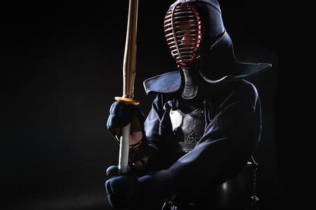 Kendo fighter in helmet holding bamboo sword on black Stok Fotoğraf