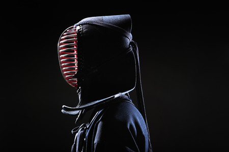 Side view of kendo fighter in traditional helmet on black