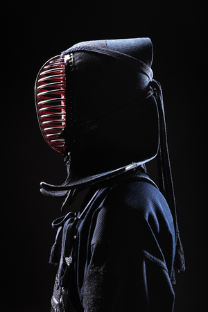 Side view of kendo fighter in traditional helmet isolated on black