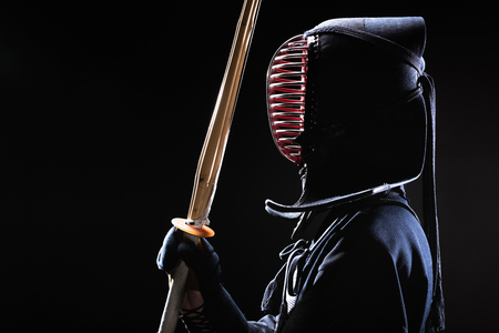 Side view of kendo fighter in traditional helmet holding bamboo sword on black