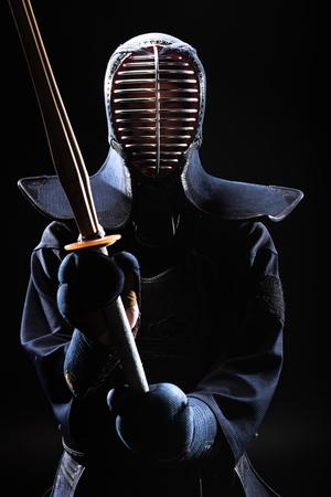Kendo fighter in helmet holding bamboo sword on black Imagens - 119967380