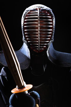 Kendo fighter in helmet holding bamboo sword isolated on black