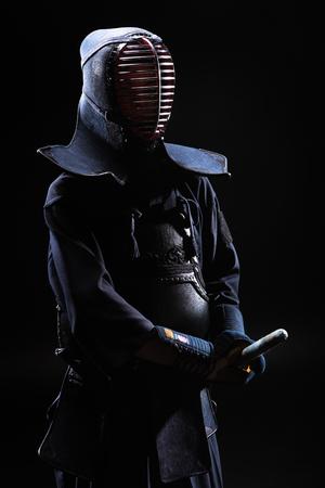 Kendo fighter in helmet holding bamboo sword on black Stock Photo