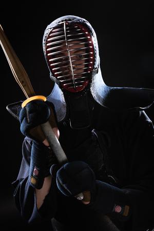 Kendo fighter in helmet holding bamboo sword on black Stok Fotoğraf - 119967389