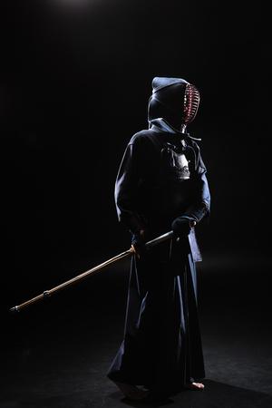 Full length view of kendo fighter in helmet holding bamboo sword on black