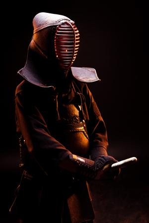 Kendo fighter in armor and helmet standing on black