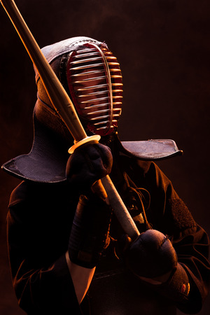 Kendo fighter in armor holding with bamboo sword on black Stok Fotoğraf