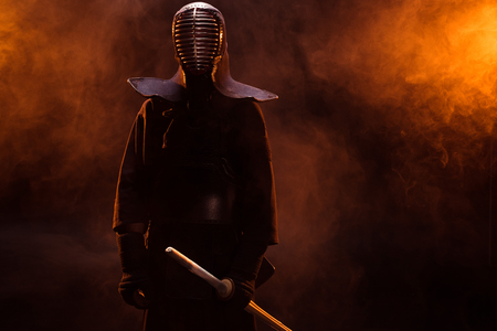 Kendo fighter in armor holding bamboo sword in smoke