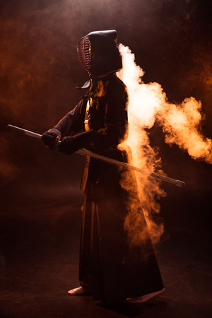 Full length view of kendo fighter in armor holding bamboo sword in smoke Stok Fotoğraf - 119967521