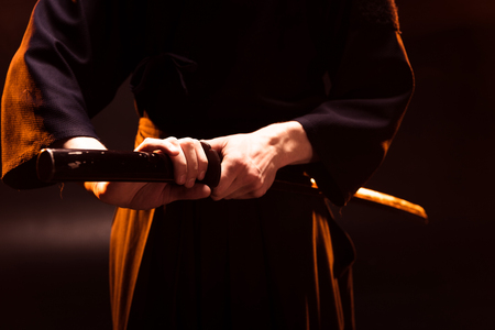 Partial view of kendo fighter holding bambo sword on black Banco de Imagens