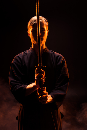 Young man in kimono holding kendo sword on black