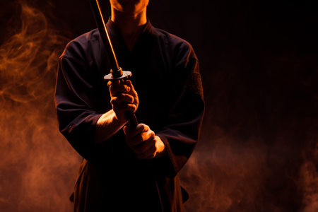 Cropped view of young man in kimono holding kendo sword in smoke
