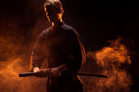 Young man in kimono holding kendo sword in smoke