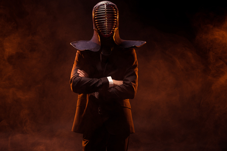 Kendo fighter in formal wear and helmet standing with crossed arms on dark