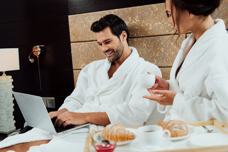 handsome man using laptop in bed near beautiful girlfriend with cup of coffee