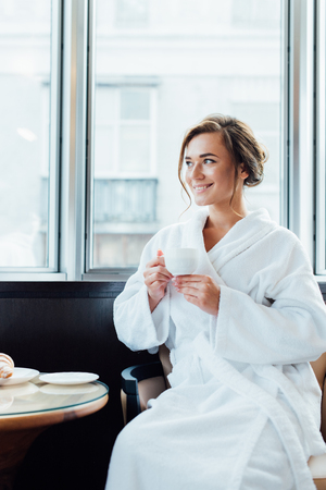 attractive brunette woman in bathrobe sitting and holding cup of coffee