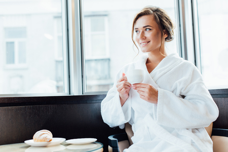 attractive brunette woman in bathrobe smiling and holding cup of coffee