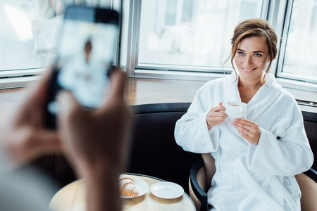 cropped view of man taking photo of attractive girlfriend holding cup while sitting in bathrobe in hotel Archivio Fotografico