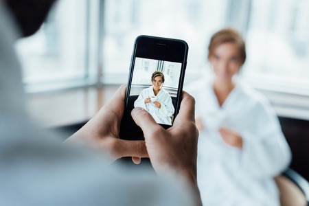 selective focus of man taking photo of attractive girlfriend holding cup while sitting in bathrobe in hotel
