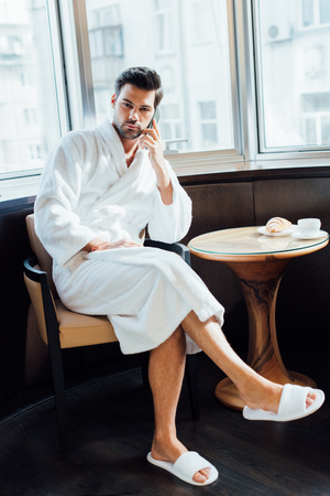 handsome bearded man in white bathrobe sitting on chair and talking on smartphone