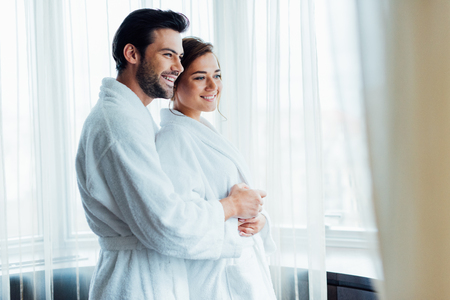 selective focus of cheerful man hugging happy woman in white bathrobe in hotel