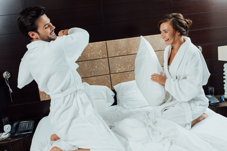cheerful couple having pillow fight on bed in hotel