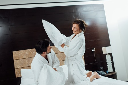happy couple having pillow fight on bed in hotel