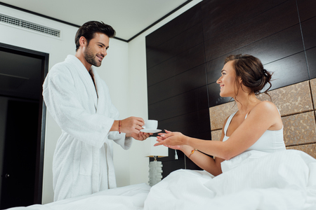handsome bearded man giving cup of coffee to beautiful woman in bed
