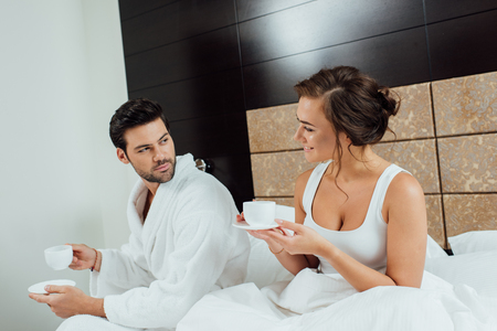 handsome bearded man and beautiful woman looking at each other while holding cups Stock Photo