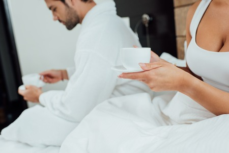 cropped view of woman and man holding cups with coffee in bed Stock Photo