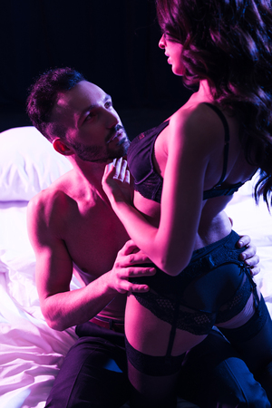 passionate man touching woman in sexy underwear isolated on black