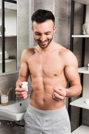 happy shirtless man looking at dental floss while standing in bathroom
