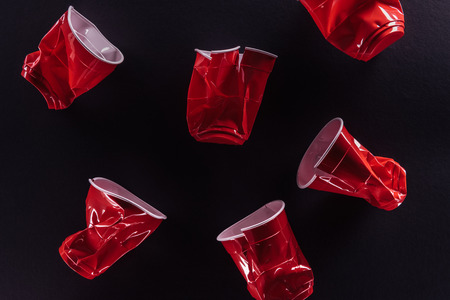Red plastic cups isolated on a black background