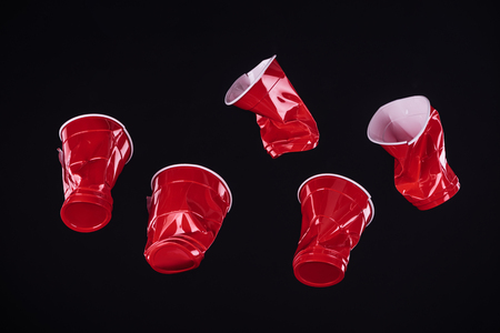 top view of bright and colorful, red plastic cups isolated on black with copy space Stock Photo