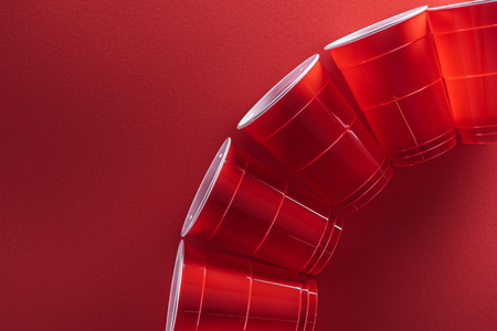 flat lay with bright and colorful plastic cups on red background with copy space
