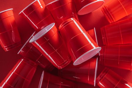 top view of bright and colorful plastic cups on red background