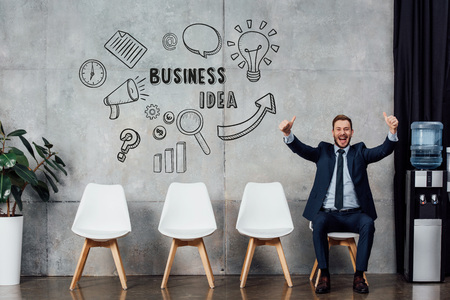 excited businessman in suit sitting and showing thumbs up in waiting hall with business idea lettering on wall