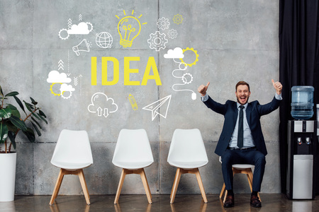 excited businessman in suit sitting and showing thumbs up in waiting hall with idea lettering on wall