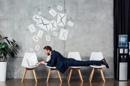 businessman lying on chairs and using laptop in waiting hall with e-mail illustration on wall Stock Photo