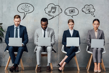 multiethnic businesspeople sitting on chairs and using laptops in waiting hall with speech and thought bubbles illustration above heads