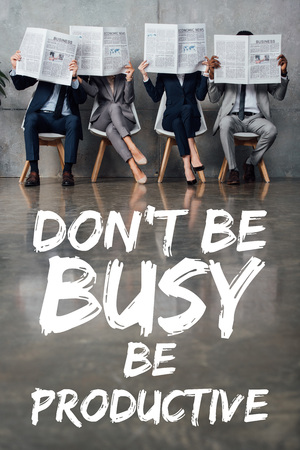 businesspeople sitting on chairs and holding newspapers in front of faces in waiting hall with dont be busy be productive lettering on floor Stock fotó