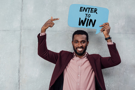 smiling african american casual businessman looking at camera and pointing with finger at speech bubble with enter to win lettering