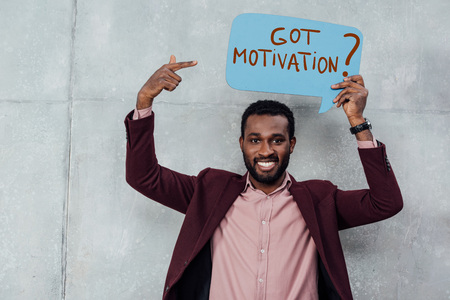 smiling african american casual businessman looking at camera and pointing with finger at speech bubble with got motivation question Banque d'images - 119969487
