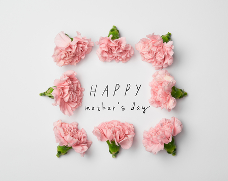 top view of floral frame made of pink carnations on white background with happy mothers day lettering