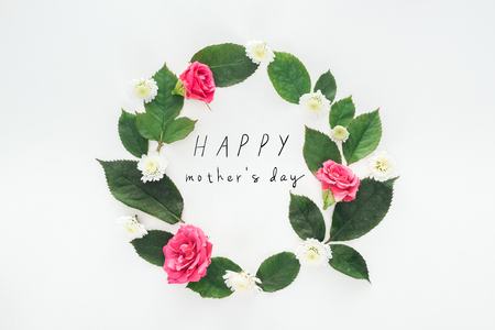 top view of circular composition with green leaves, roses and chrysanthemums on white background with happy mothers day illustration