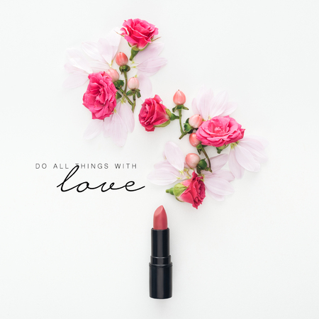 top view of composition with roses, buds and petals with lipstick on white background with do all things with love lettering Фото со стока