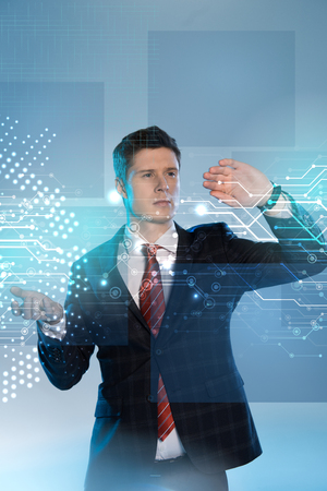 handsome businessman in suit pointing at network illustration in front on blue background
